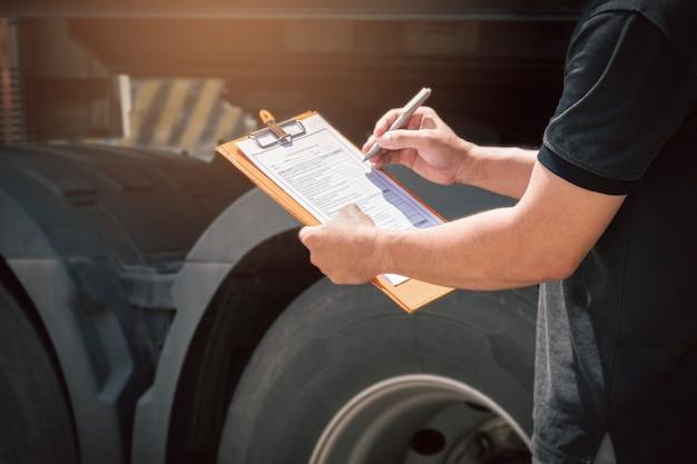 Kierowca ciężarówki trzymający schowek sprawdzający codzienną listę kontrolną
