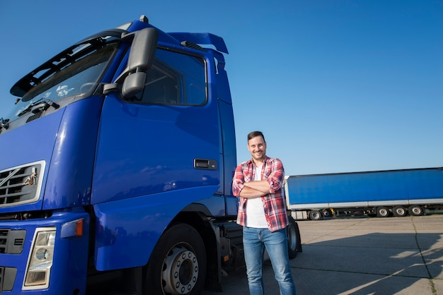 Kierowca ciężarówki w zwykłym ubraniu stoi obok swojej ciężarówki z rękami skrzyżowanymi na postoju