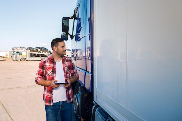 Kierowca ciężarówki w zwykłym ubraniu stoi przy ciężarówce z tabletem i patrzy na ciężarówkę