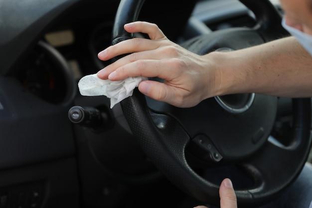 Kierowca czyści kierownicę swojego samochodu za pomocą ściereczki antybakteryjnej. koncepcja antyseptyki, higieny i opieki zdrowotnej. selektywna ostrość