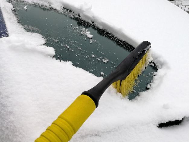 Kierowca czyści przednią szybę samochodu szczotką z grubej pokrywy śniegu.