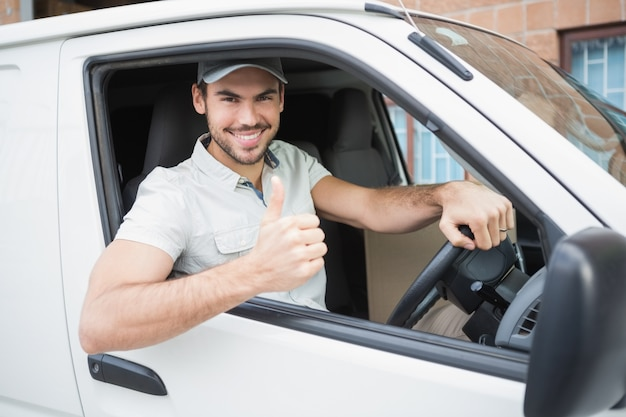 Kierowca dostawy pokazuje kciuki do góry prowadzenie swojej furgonetki