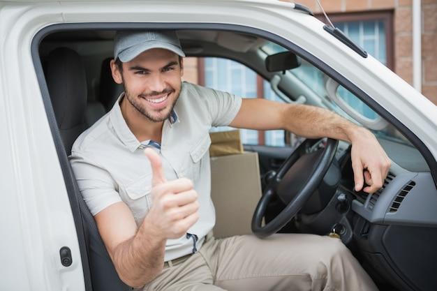 Kierowca dostawy uśmiecha się do kamery w jego van