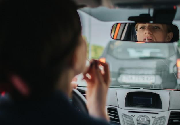Kierowca jedzie w drodze, rozmawia przez telefon, pracuje z dokumentami i jednocześnie robi makijaż. bizneswoman robi wiele zadaniom. wielozadaniowość kobieta biznesu.