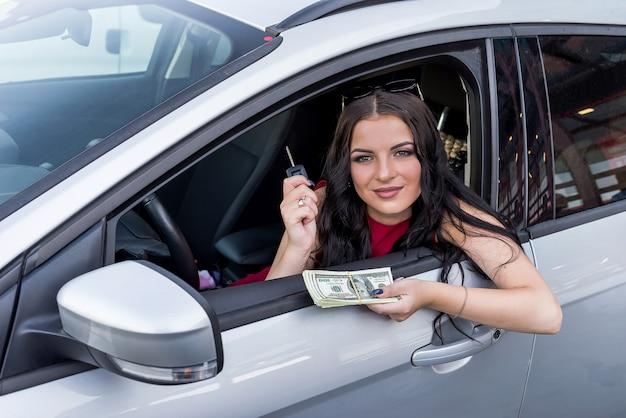Kierowca kobieta pokazuje dolary i kluczyki do samochodu z okna