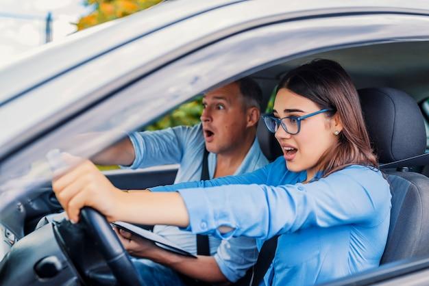 Kierowca kobieta - wypadek samochodowy, krzyczy ze strachu lub frustracji. studencka dziewczyna siedzi okaleczająca wewnątrz