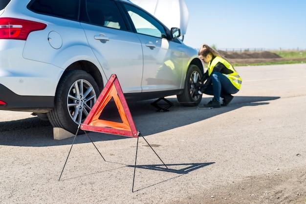 Kierowca kobieta zmienia uszkodzone koło na poboczu drogi
