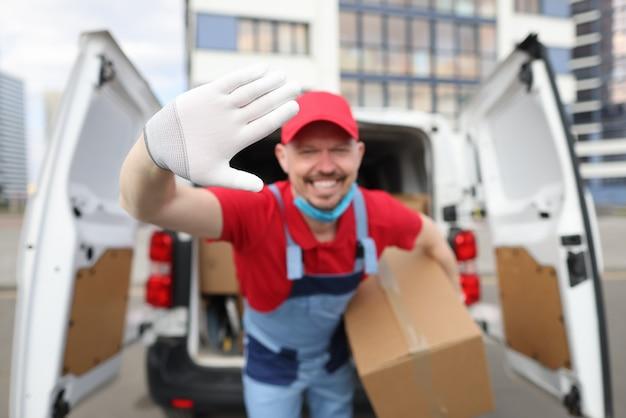 Kierowca kurier w mundurze uśmiecha się i macha w dłoni trzymając w dłoni kartonowe pudełeczko