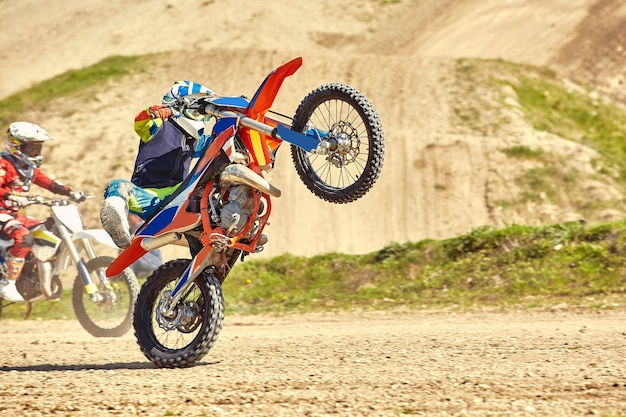 Kierowca motocrossu w akcji przyspieszający motocykl startuje i wskakuje na trampolinę na torze wyścigowym