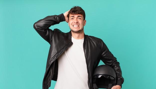 Kierowca motocykla czuje się zestresowany, zmartwiony, niespokojny lub przestraszony, z rękami na głowie, panikujący z powodu błędu