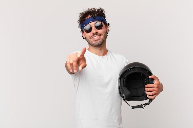 Kierowca motocykla wskazujący na aparat z zadowolonym, pewnym siebie, przyjaznym uśmiechem, wybierający ciebie