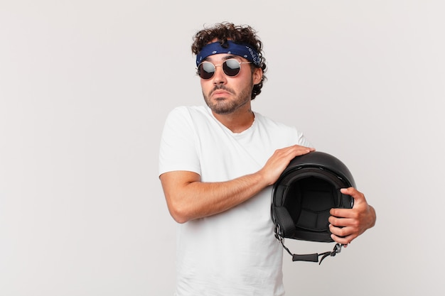 Kierowca motocykla wzrusza ramionami, czuje się zdezorientowany i niepewny, wątpi ze skrzyżowanymi ramionami i patrzy na zdziwienie