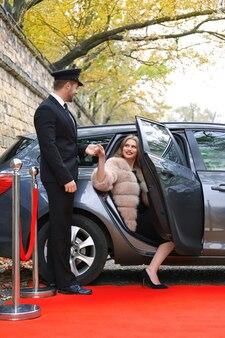 Kierowca pomaga pięknej młodej kobiecie wysiąść z samochodu na czerwonym dywanie