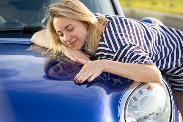 Kierowca średniej kobiety obejmujący maskę samochodu po uszczegółowieniu reklamy ubezpieczenia samochodu