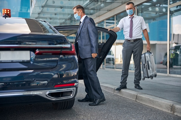 Kierowca trzyma walizkę, pomagając biznesmenowi wsiąść do samochodu po przyjeździe w maskach