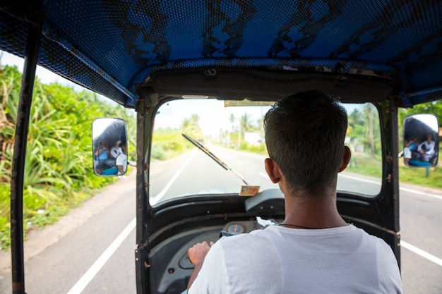 Kierowca tuk tuk na drodze sri lanki, widok z samochodu. cejlon tradycyjny transport turystyczny, lokalna taksówka
