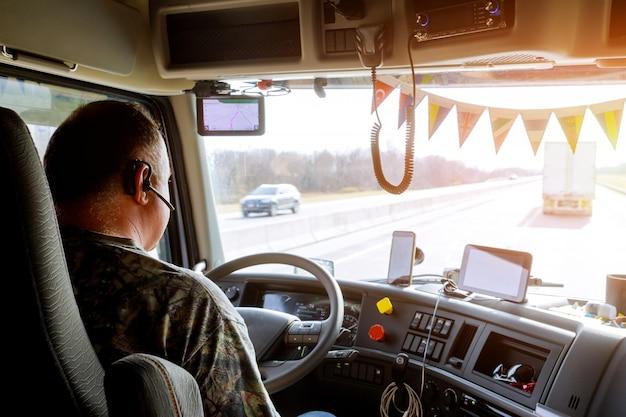 Kierowca w kabinie dużej nowoczesnej ciężarówki