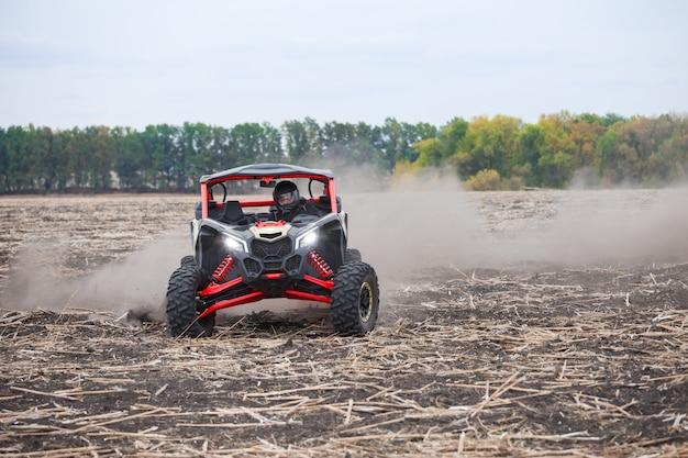 Kierowca w kasku na quadzie na zaoranym polu