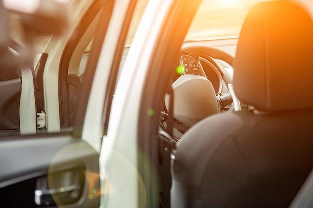 Kierownica i puste siedzenie kierowcy nowego suv premium widziane z tylnych drzwi. selektywne skupienie. siedzenie kierowcy w słońcu