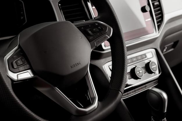 Kierownica nowego pojazdu z bliska, wnętrze kokpitu, przyciski elektryczne