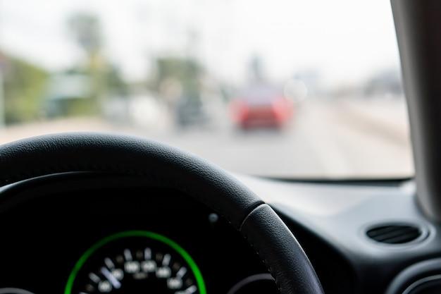 Kierownica przed interfejsem samochodu z widokiem ruchu drogowego