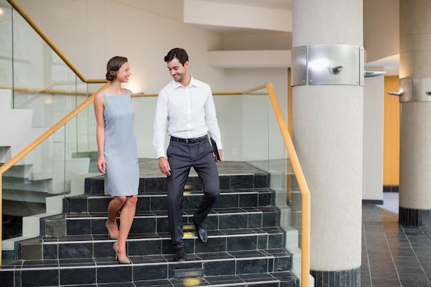 Kierownictwo firmy schodzi po schodach w centrum konferencyjnym