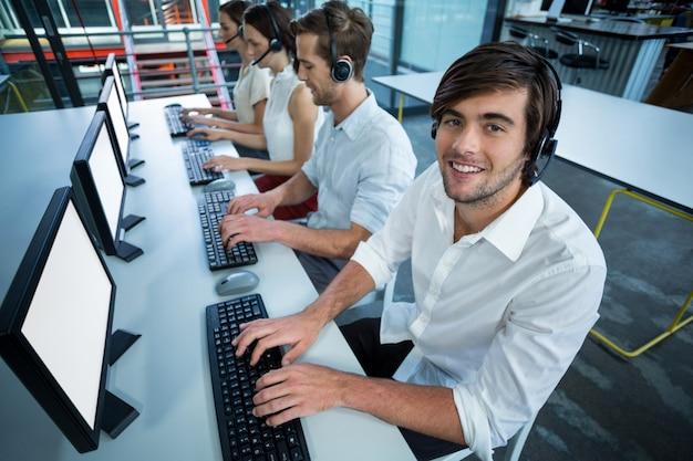 Kierownictwo firmy ze słuchawkami za pomocą komputera