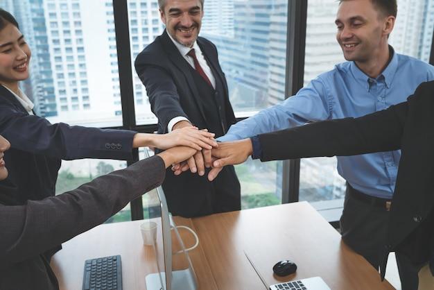 Kierownictwo i młodzi pracownicy zespołu biznesowego łączą ręce po spotkaniu w biurze