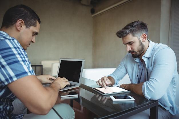 Kierownictwo korzystające z laptopa i tabletu cyfrowego w kafeterii