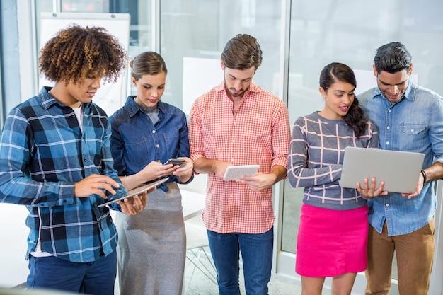 Kierownictwo korzystające z laptopa, tabletu cyfrowego i telefonu komórkowego