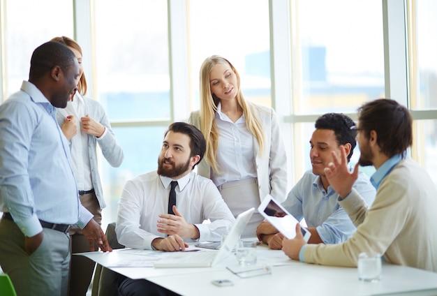 Kierownictwo z cyfrowym tablecie o spotkanie w biurze