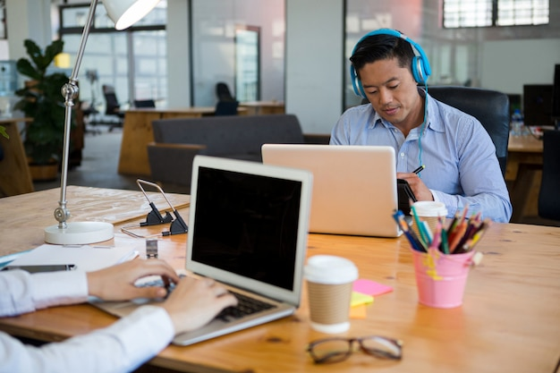 Kierownicy biznesowi za pomocą laptopa przy biurku