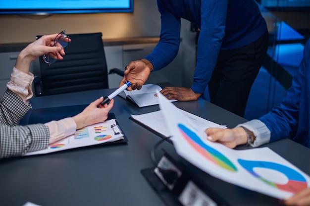 Kierownicy na negocjacje biznesowe w biurze nocnym. pracowników płci męskiej i żeńskiej, ciemne wnętrze centrum biznesowego, nowoczesne miejsce pracy