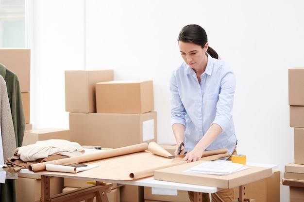 Kierownik biura sklepu internetowego stojąc przy stanowisku pracy i wycinając papier pakowy do pakowania zamówień klientów
