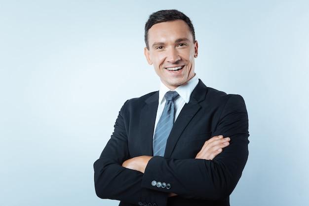 Kierownik biura. szczęśliwy pozytywny przystojny mężczyzna stojący krzyż uzbrojony i uśmiechnięty podczas pracy jako kierownik biura
