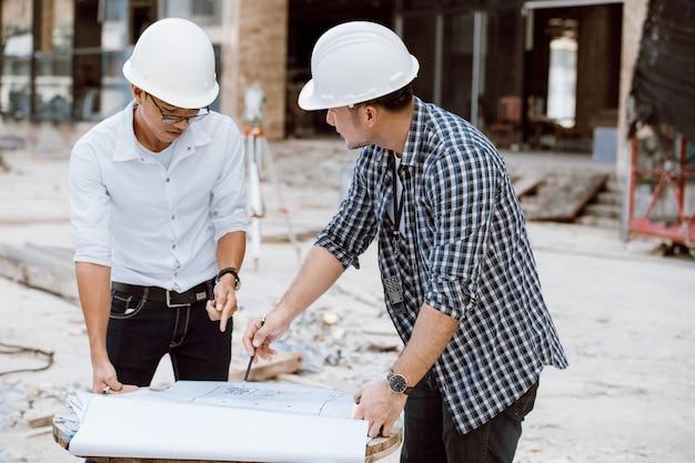 Kierownik budowy i zespół inżynierów sprawdzający plan na budowie. sprzęt tranzytowy teodolitu. zespół inżynierów. praca na budowie.
