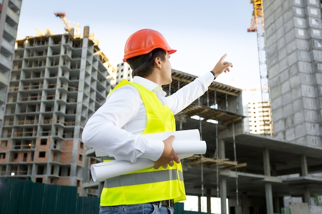 Kierownik budowy w kasku sprawdzający plac budowy w budowie