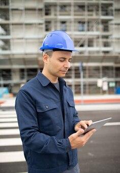Kierownik budowy za pomocą tabletu przed placem budowy