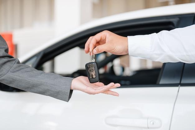 Kierownik daje kobiecie klucz do nowego samochodu w salonie.
