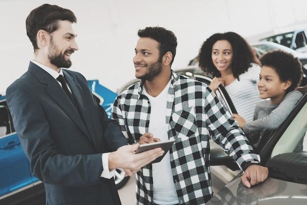 Kierownik ds. transakcji samochodowych i właściciel gotowy do podpisania dokumentów.