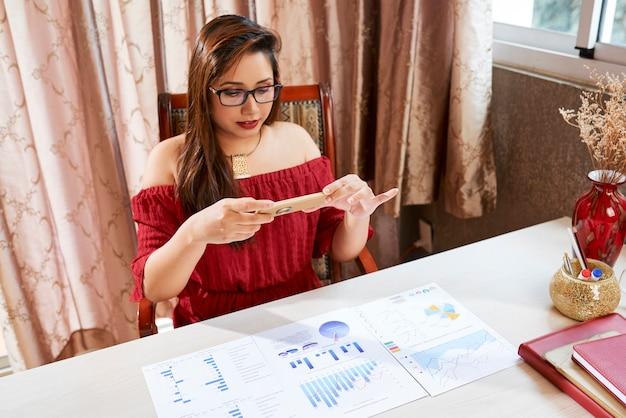 Kierownik działu marketingu robi zdjęcie na raportach i wykresach na swoim stole, aby wysłać je koledze
