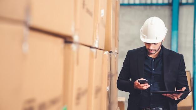 Kierownik fabryki korzystający z komputera typu tablet w magazynie lub fabryce
