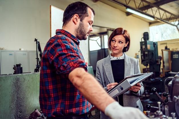 Kierownik fabryki rozmawia z niezadowolonym pracownikiem