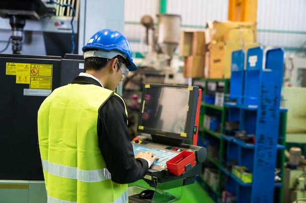 Kierownik fabryki używa komputera do sprawdzenia maszyny