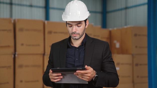Kierownik fabryki za pomocą komputera typu tablet w magazynie lub fabryce