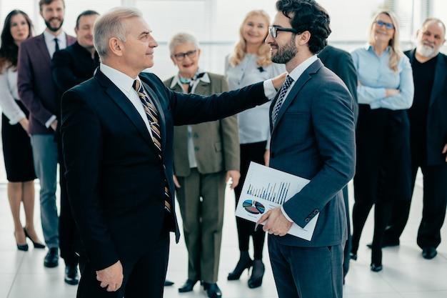Kierownik gratuluje najlepszemu pracownikowi na spotkaniu