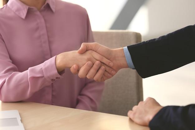 Kierownik i klient, ściskając ręce w biurze, zbliżenie