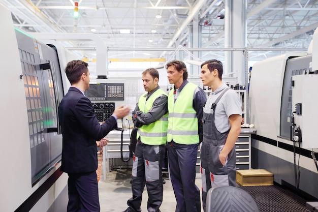 Kierownik i pracownicy w zakładzie przy maszynach cnc