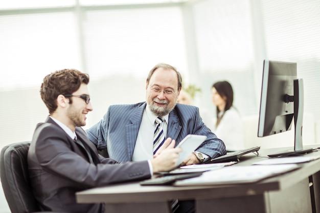 Kierownik i pracownik omawiają dokumenty biznesowe w miejscu pracy.
