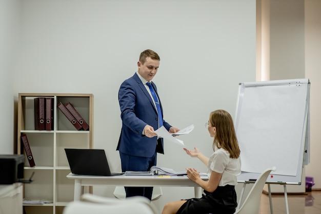 Kierownik i sekretarka pracująca w biurze.